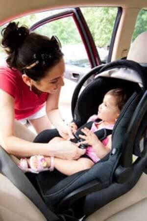 A mother strapping her baby into a car seat