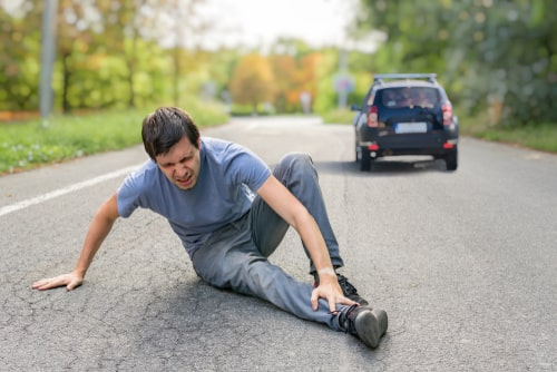 Man sitting on the road holding his lower leg